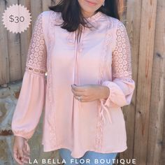 Pink long sleeve blouse with lace details along the sleeves. Wide-length sleeves feature tie closures at wrists and along the neckline. Relax fit.
