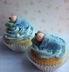 Baby shower cupcakes with miniature of baby on cute little blue bed.