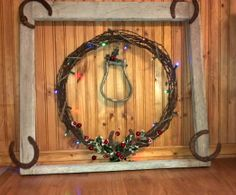 Barbed wire wreath inside an old Window frame with horseshoes.