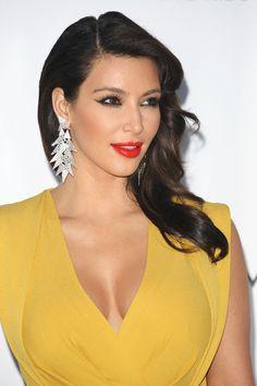 Kim Kardashian vestido amarillo labios rojos cabello castaño oscuro largo pendientes plateados y blancos