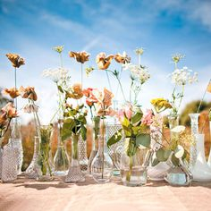 Vases filled with wildflowers and paper flowers that the bride had fashioned from vintage romance novel pages were on display during the ceremony. All of the fresh floral arrangements were by Trellis Weddings.  Photo by Tim Tab Studios. #weddings #rustic #diy
