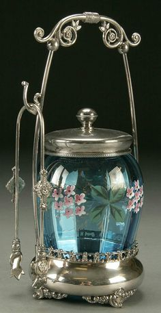 "VICTORIAN COBALT PICKLE CASTOR, late 19th century, optic ribbed blue body decorated with pink flowers and green leaves set in an embossed leaf scrolling silver-plate holder, together with ornate tongs, stamped ""Forbes Silver Co."" Height 10""."