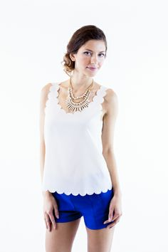 white tank top has scallop lining on the hemline and the neck and shoulders