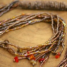 Fair Trade Beaded Tie Necklace — handmade in India — find it at http://fairandsquareimports.com/jewelry/beaded-tie-necklace-india — This multi-strand necklace features brown, gold & burgundy glass beads, with tiny stones scattered throughout. Wear loose or tied.