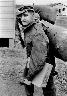 Elvis Presley being new in the army carries a few duffle bags over his right shoulder at Ft. Chaffee,Arkansas in March 1958