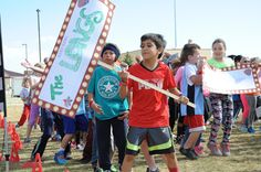 "Third-grader Mauricio Delgado, 8, holds a class sign before a fundraiser April 15 at Ridgeview Elementary School.  Hosted by Boosterthon, the fundraiser culminated in a run where students received pledges for completing each lap, raising money for technology at the elementary school. According to their website, Boosterthon provides ""a fun, healthy alternative to sales-driven fundraisers."""