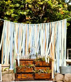 Use a rustic-looking ribbon backdrop to break up a large open space at an outdoor reception.