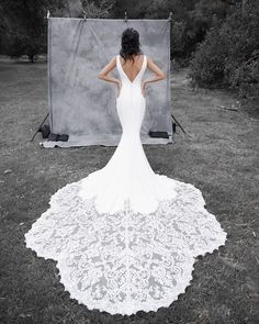 Available at www.theweddingdresscompany.co.uk Fitted crepe plain Enzoani wedding dress with really long lace train and low back