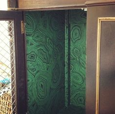 Inside of Erin Gates bar cabinet, wallpapered with Fornasetti Malachite paper from Cole & Sons