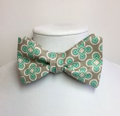Mens seafoam green print fabric with a grey background bow tie - 100% premium cotton, Pre-tied bow tie has a white strap that adjusts from 12 - 18  Freestyle or self-tie bow tie features an adjustable strap that ranges from 12 - 17  Infant & Boys bow ties can be made either clip-on or with a velcro strap. Please specify preference when ordering.  Girls hair bows is a cute double-layer bow that attaches with an alligator clip. It comes in three sizes, small - medium - large. Please specif...