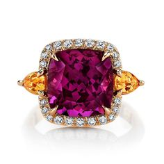 Not your grandmother's garnet ring.......this 6.5 carat rhodolite garnet cushion is flanked by spessartite garnet pear shapes.