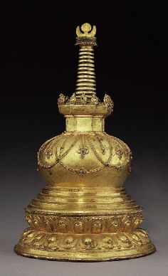A Large Gilt Bronze Stupa   Tibet, 15th Century   The base with a double-lotus frieze with beaded rim, rising to a stepped plinth supporting the dome adorned with beaded garlands and pendent jewels inset with turquoise, the square harmicka crowned with flaming jewels supporting the conical parasols with moon and sun finial, richly gilt overall, the base with original seal and stippled with a double-vajra  15½ in. (39.5 cm.) high