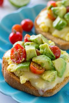 A fresh avocado cherry tomato salad is piled high over crisp toast, fluffy scrambled eggs and lots of melty cheese for one impressive, yet easy breakfast!