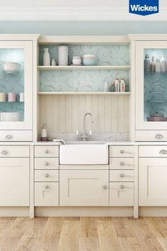Create a modern country kitchen by combining a crisp white Lyskam Quartz worktop with the creamy tones of a shaker style cabinet. A deep bowl Belfast sink is the perfect choice for a country kitchen, draw extra attention to the feature with on-trend open shelving above. Wallpaper inside glass fronted cabinets oozes true uniqueness.
