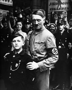 "Donald and ""Uncle Adolf"" at a rally in 1939. Donald learned a lot from his ""Uncle,"" but decided to switch out the hat for his now famous red cap. Hitler thought he was making a mistake, but Donald insisted that he would someday make America Great Again, and become President. Hitler thought Donald was ""Shtupit,"" but played along because he thought the boy was a perfect patsy and ""nasty little Nazi."""