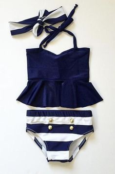 Nothing beats nautical style at the beach!? Retro styling with a nautical tankini and button detail is a timeless look. Complimentary headband while supplies last! Please note: This is a PRE-ORDER & takes approximately 3 weeks to ship out!