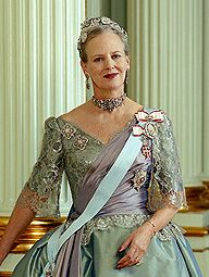 The Queen of Denmark shown in a Gala gown by Jørgen Bender, 1995. The sleeves and the bodice are ornamented with silver lace and draped with violet silk taffeta.