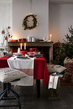 nappe de table rouge, chemin de table blanc à rayures rouges, vaisselle rouge et chandelles blanches à côté du sapin de Noël naturel
