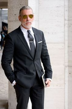 Nick Wooster in black herringbone notch lapel suit. Solid charcoal tie, tie bar, white linen pocket square