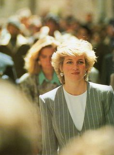 Spain in April 1987, the Princess of Wales wears a collarless double-breasted grey and white pinstripe suit by Catherine Walker.