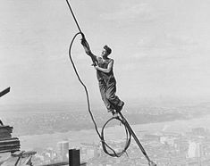 Construction worker above Manhattan. Empire State Building. Circa 1920's. Photographed by Lewis Hine.