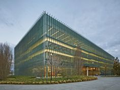 The sloping floor is legible from the completely glazed exterior, whose fritted, 2-foot-deep glass fins serve as an external shading device and transfer wind loads.