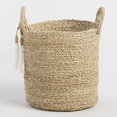 Crafted of seagrass, outfitted with loop handles and accented with white rope tassels, our casual storage tote is naturally warm and effortlessly chic.