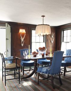 The dining room has a warm, cozy feeling. George III chairs are upholstered in a cheerful blue cotton from Shyam Ahuja.