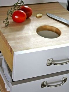 Cutting board drawer with hole over a trash can.