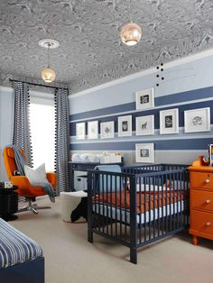 An eclectic mix of color and pattern provides plenty of stimulation in this stylish nursery. A stunning patterned ceiling with two pendant lights is the highlight, while a blue striped wall and fun pops of orange liven up the space.