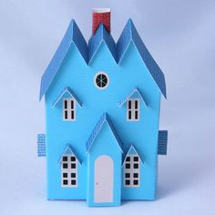 A 1:144 or N scale Putz house with three gables for a traditional railroad Christmas village.