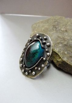 This handmade, statement ring is made with a colorful 18x24mm natural chrysocolla cabochon. The chrysocolla possesses warm hues of green, black,
