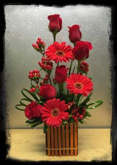 Red roses, red gerbera daisies, and hypericum floral arrangement in a cute fence cube