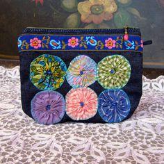 Handmade denim pouch with vintage yo-yo's and floral woven trim.
