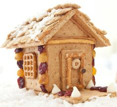 """CUTE idea for a """"healthier"""" gingerbread house from familyfunmag.com: Graham crackers and peanut butter """"glue"""" form the walls of this cute, non-traditional """"gingerbread"""" house you can then decorate with cereal, nuts and dried fruit."""