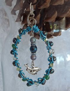 For all those who love the sea life, dolphins and the ocean.  This is for you.    This is a handmade wire wrapped pendant made with genuine Freshwater Cultured Pearls, Blue Topaz, Green Aventurine and Peridot gemstones.  It's wrapped with colored copper wire.  It has a dolphin charm dangling fr...