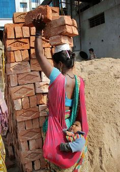 This image showing a hardworking mother in India carrying six bricks on her head while bal. We Are The World, People Around The World, Our World, Mundo Cruel, Amazing India, Mother And Child, Image Shows, World Cultures, Baby Wearing