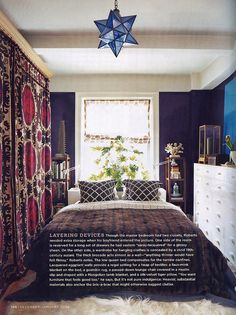 Beautiful rich colors in a small bedroom but organized with lots of visual layering.