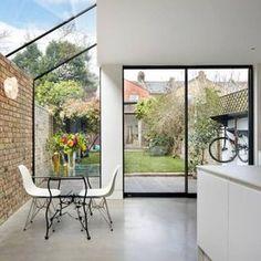 Com uma extensão de vidro, a cozinha e a sala de jantar desta casa em Londres ganharam vista para o verde e luz natural