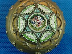 """Antique Italian Floral & Fans Micro Mosaic Trinket/Pill Box. -- Early, old style, Italian micro mosaic (tiny tesserae) brass box made by the Italian mosaic artisans of old. A Bouquet of Flowers circled by green leaves & turquoise triangles with stars.  The tiny """"micro"""" tesserae are millefiore glass rods, some of 5 colors. Circling the bouquet are 6 unfolded ladies fans of 2 color glass millefiore rod, white & lavender. Fine Murano Italy glass work typical of late 19th century. 
