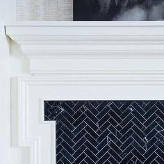 White Greek Key Fireplace Mantle with Black Herringbone Tile Surround