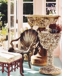 Shell encrusted pedestals in the sun room. Not to miss, the shell shaped chair and the faux bamboo chair with red coral.