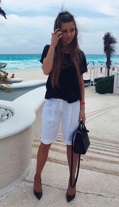 Street style look com polo preta, bermuda social branca e scarpin.