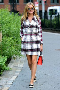 Olivia Palermo wears a plaid vest belted at the waist and over a plaid shirt with tan flats, a structured color-block bag and sunglasses.