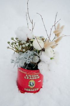 Rustic winter floral arrangement in an old tobacco tin #rustic #winter #centerpiece