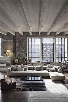 Concrete ceiling/beams, large grey sofa, large windows (b/w frames)