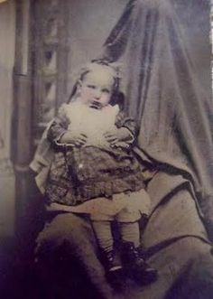 Post Mortem Photo. Child held by covered figure, the mother or father perhaps?