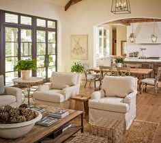 Layout - open plan, neutral, layered living room, dining room, kitchen in the background. large windows.