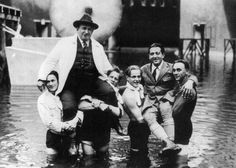 Director Fritz Lang and cinematographer Karl Freund being carried through the flooded Worker's City on the set of Metropolis, 1927