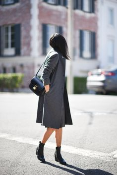 A gray coat is worn with a knee-length dress, Céline bag and ankle boots